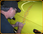 Photo of Casey Kennell pinstriping a custom hotrod